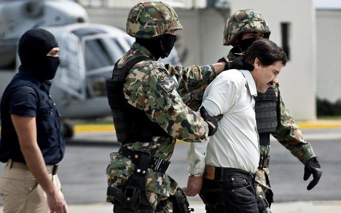 Mexican drug trafficker Joaquin Guzman Loera aka 'el Chapo Guzman', is escorted by marines as he is presented to the press on February 22, 2014 in Mexico City.
