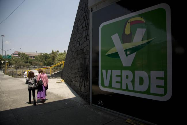 En esta imagen del 6 de abril de 2015, dos mujeres caminan junto a un cartel del Partido Verde en Ciudad de México. Aunque se presenta como una nueva solución para los problemas cotidianos del día a día, en todos los asuntos importantes el Partido Verde vota con el Partido Revolucionario Institucional del presidente, Enrique Peña Nieto. (AP Foto/Eduardo Verdugo)
